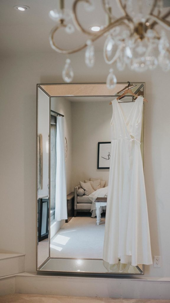 wedding dress hanging on mirror in suite at Palace Event Center | photo by Tiny Luxe Wedings