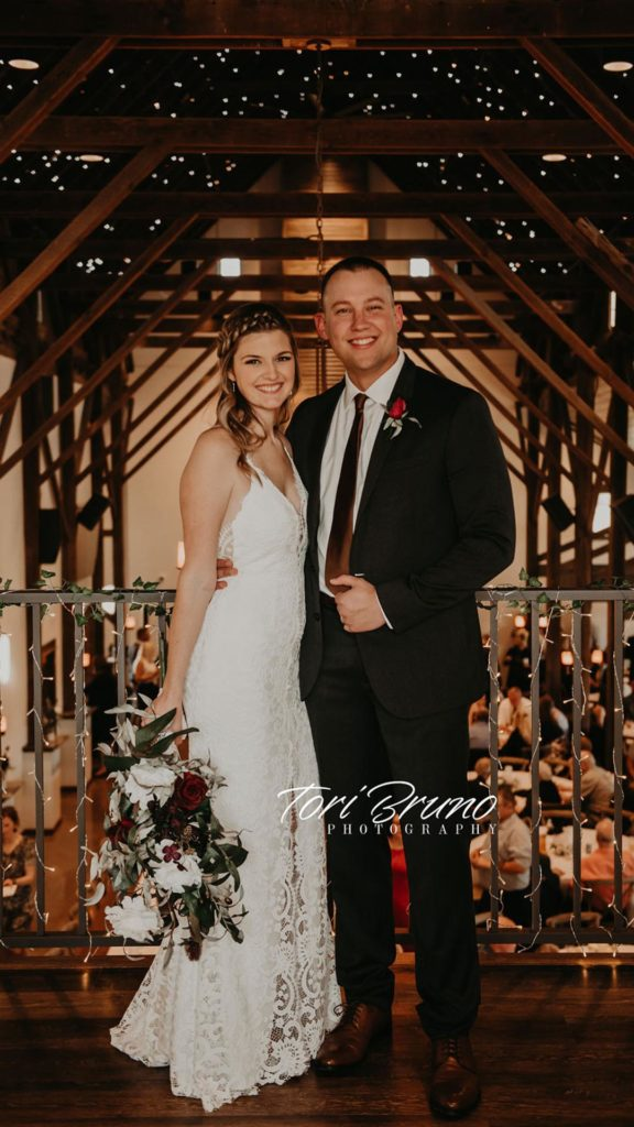 bride and groom smile together in loft at Palace Event Center | photo by Tori Bruno