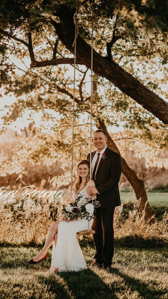 bride and groom pose together on swing at Palace Event Center | photo by Tori Bruno