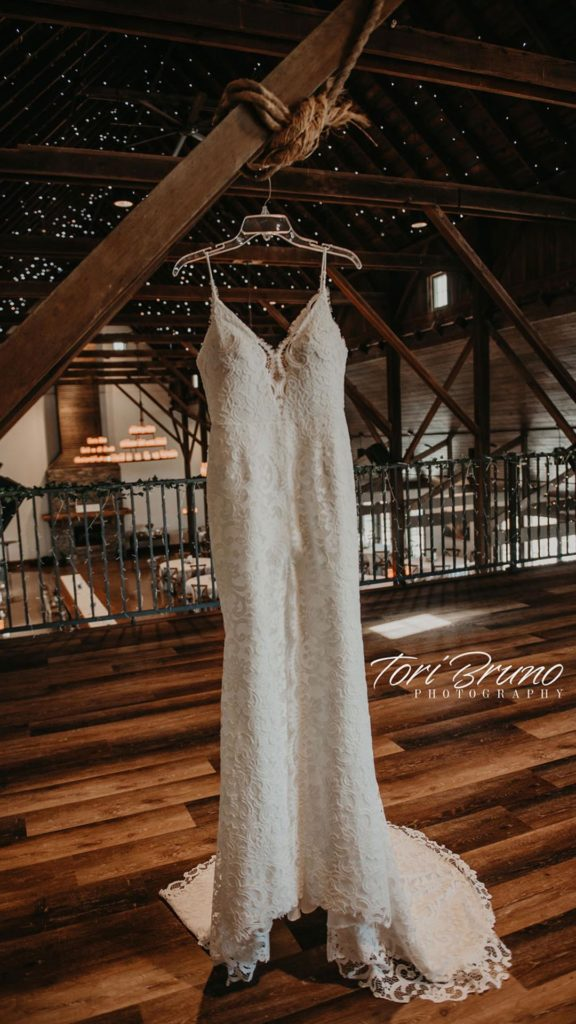 lace wedding dress hanging in loft at Palace Event Center | photo by Tori Bruno
