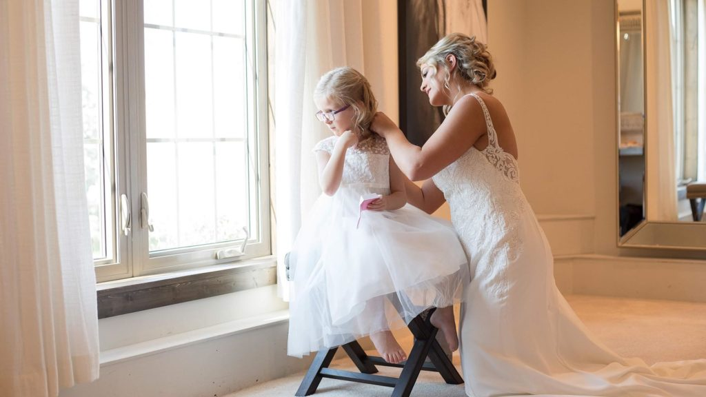 bride with flower girl in suite at Palace Event Center | photo by Get Kara'd Away