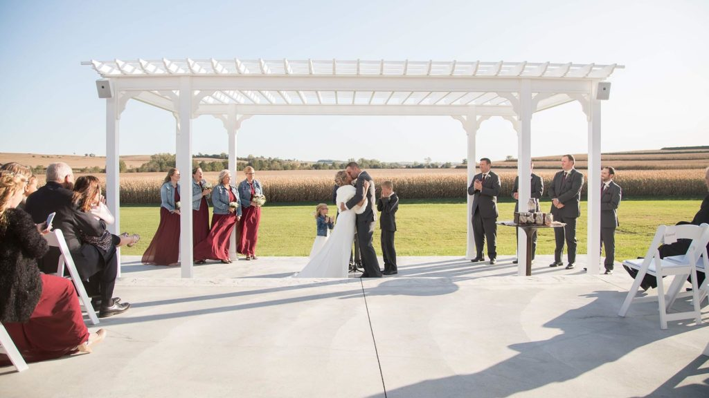bride and groom share a kiss in outdoor ceremony at Palace Event Center | photo by Get Kara'd Away