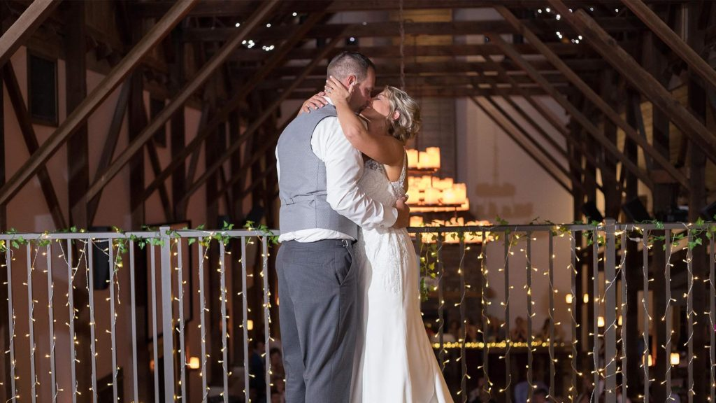 bride and groom share a kiss in loft at Palace Event Center | photo by Get Kara'd Away