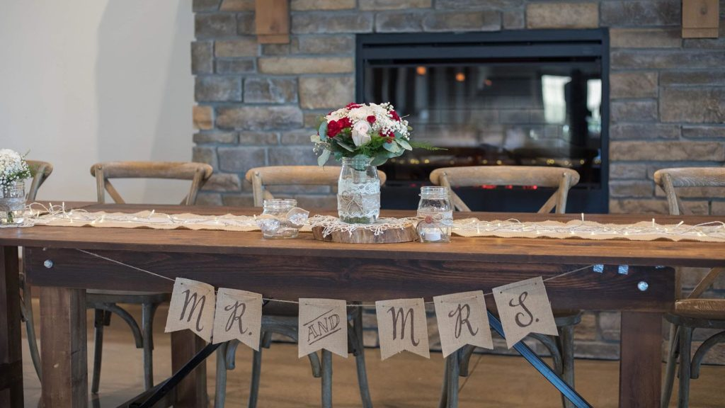 wooden head table with Mr. and Mrs. banner at Palace Event Center | photo by Get Kara'd Away