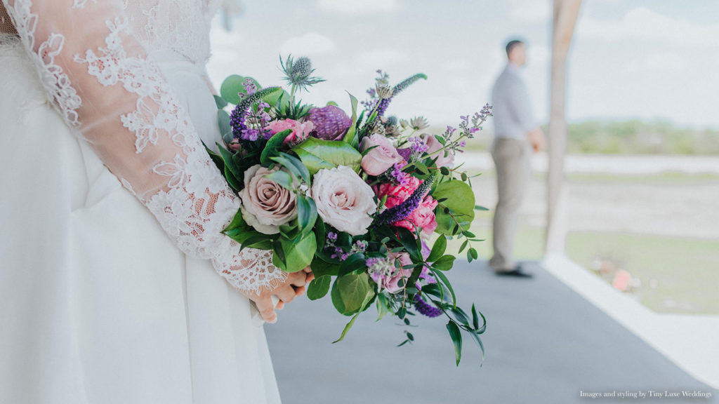 bride holds bright bouquet outside of Palace Event Center | photo by Tiny Luxe Wedings
