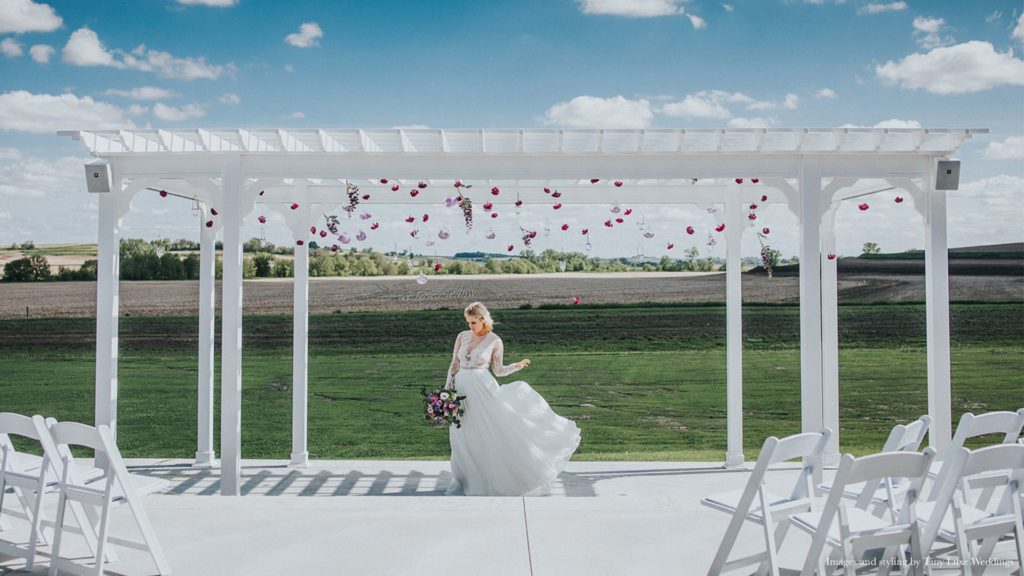 bride stands below floral decorated gazebo at Palace Event Center | photo by Tiny Luxe Wedings