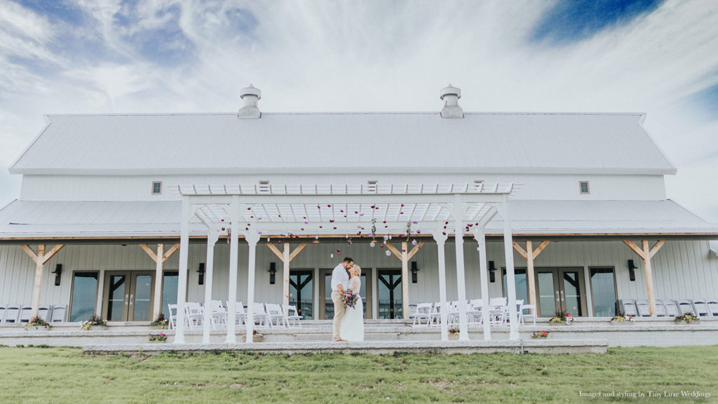 couple poses on patio for outdoor ceremony at Palace Event Center | photo by Tiny Luxe Wedings