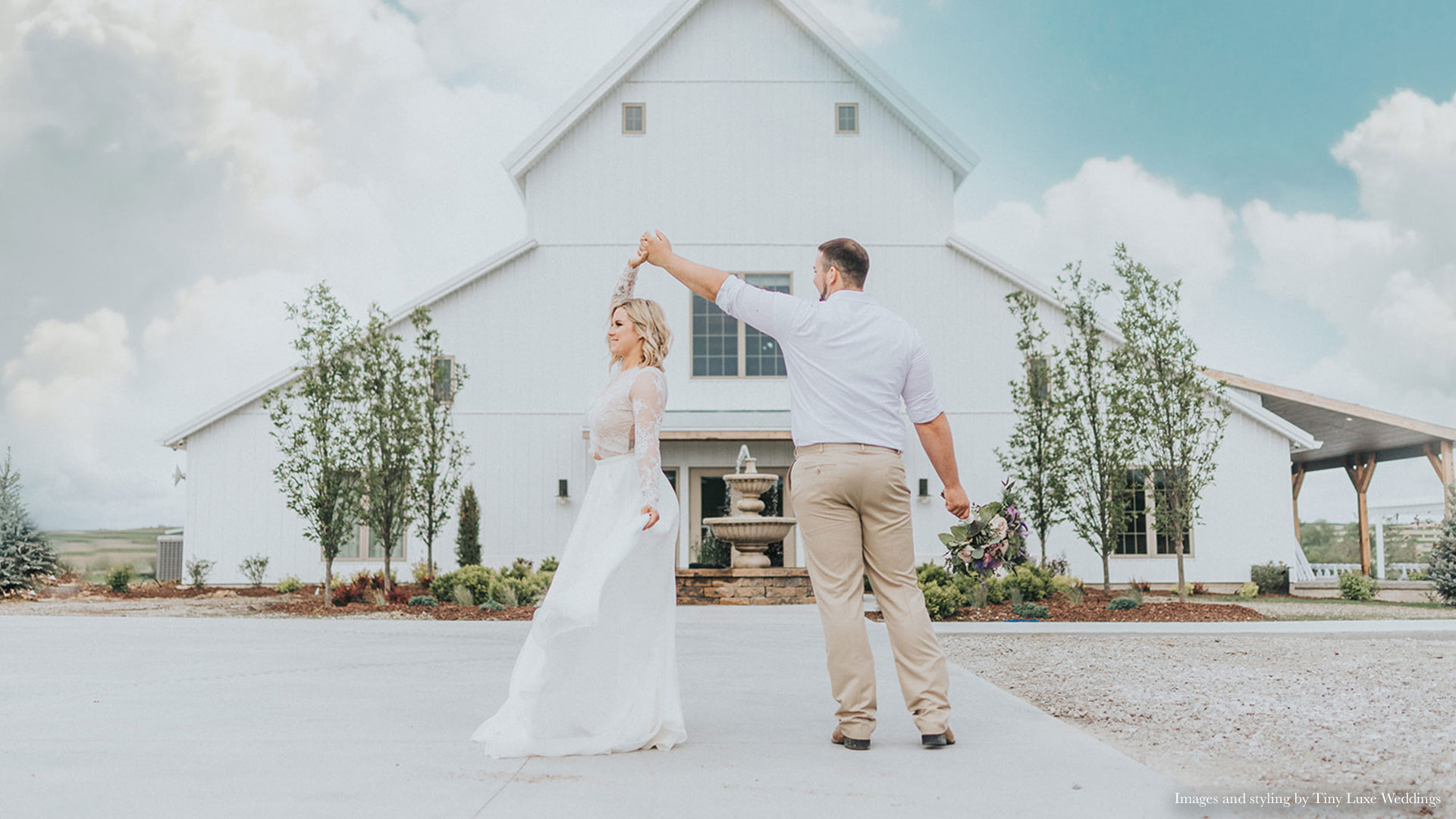 couple twirls in front of Palace Event Center barn exterior   photo by Tiny Luxe Wedings