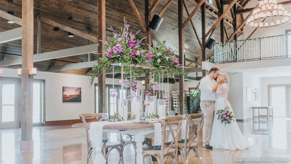 couple kissing near beautiful floral arrangement in bright Palace Event Center interior | photo by Tiny Luxe Wedings
