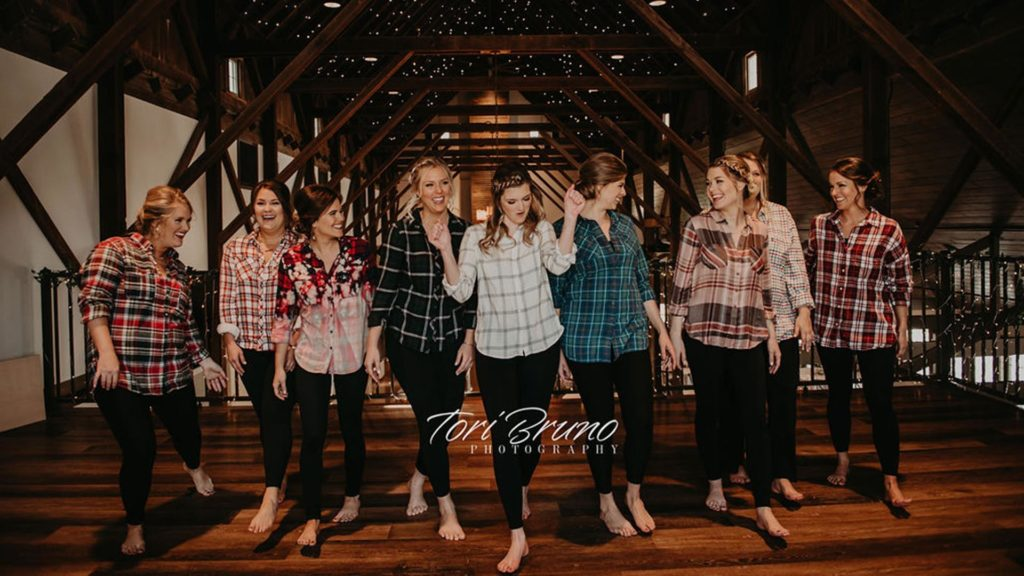 bridal party in flannel posing in loft at Palace Event Center | photo by Tori Bruno