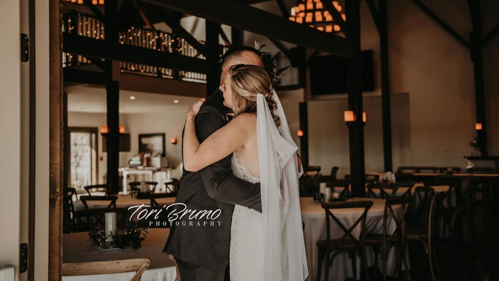 bride and groom hug at Palace Event Center | photo by Tori Bruno