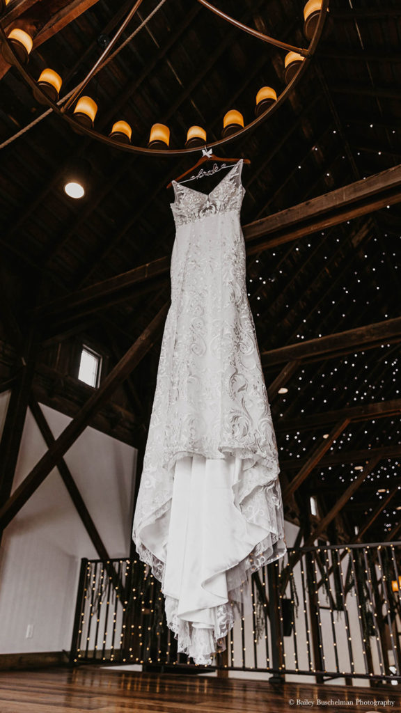 lace wedding dress hangs from loft chandelier at Palace Event Center