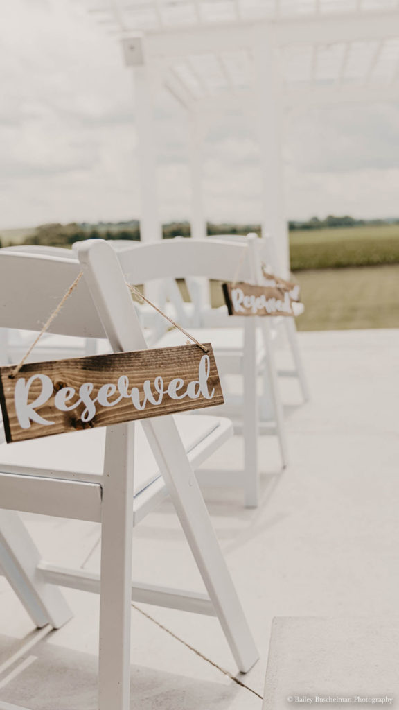 wooden Reserved sign hanging from white chair at Palace Event Center