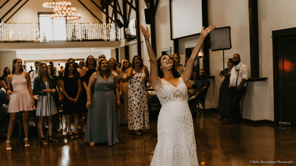 Bride throws bouquet over shoulder at wedding reception at Palace Event Center