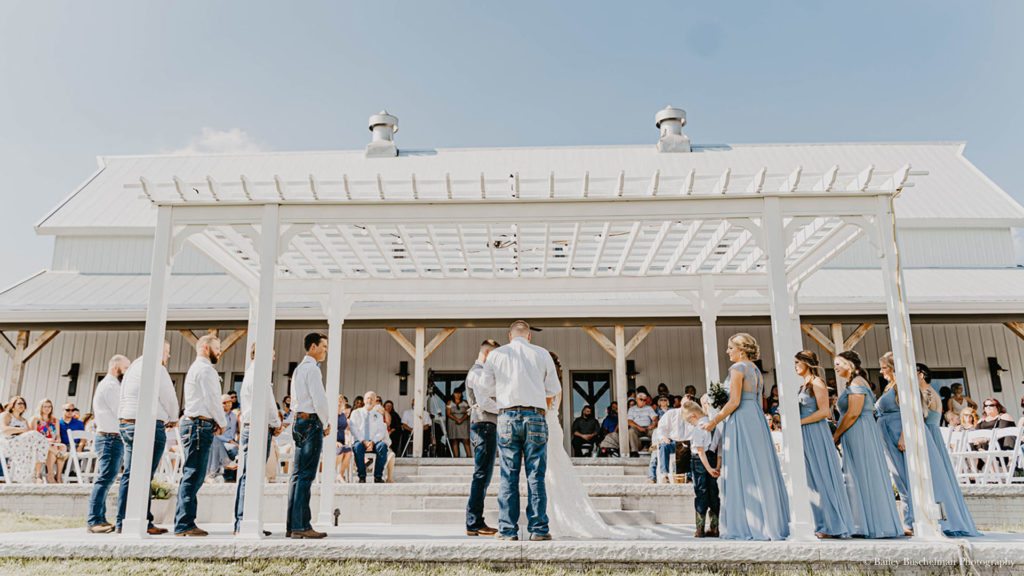 wedding party and guests watch outdoor wedding ceremony at Palace Event Center