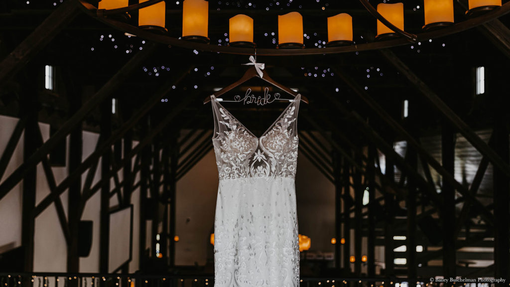 white lace wedding dress hangs in loft at Palace Event Center