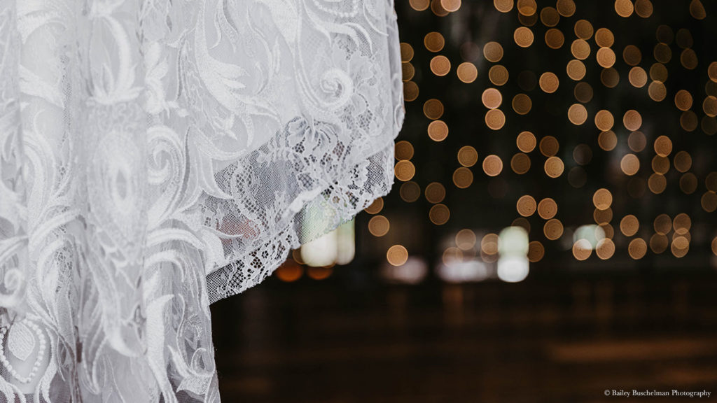 lace wedding dress detail with lights in background at Palace Event Center
